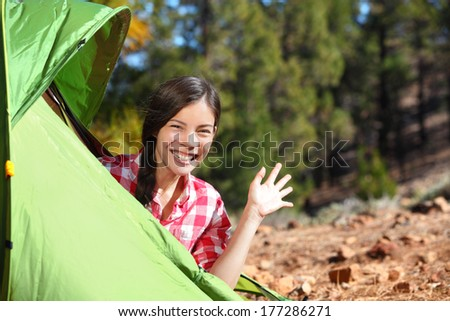 Camping woman waving hello from tent smiling happy outdoors in forest. Happy mixed race Asian Caucasian girl saying hi looking at camera. - stock photo