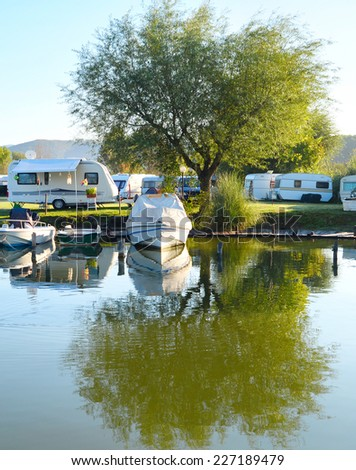 Campsite on a lake with caravans and boats - stock photo