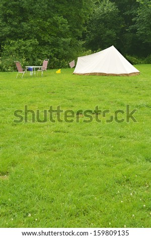 Campsite with a canvas tent mounted on grass - space for text