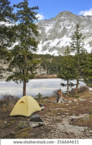 Campsite with tent in the mountains, snow capped peaks in the background - stock photo