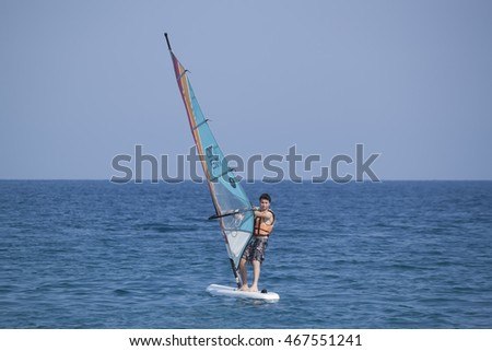 CAMYUVA, KEMER, TURKEY - JULY 11, 2015: Unidentified Turkish man glides over the waves of the Mediterranean Sea windsurfing. Extreme water sports are increasingly popular on the beaches of Turkey