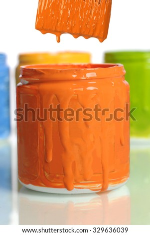 Can of orange paint in front of other containers isolated over white background - stock photo