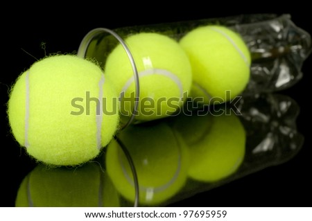 Can of three new tennis balls isolated on black background.  Shallow DOF w/focus on foreground ball.
