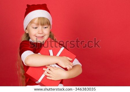 Canâ??t wait to open her present. Half length portrait of a pretty little girl wearing Santa Claus outfit looking at her present and smiling copyspace on the side - stock photo