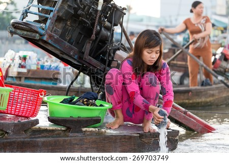 CAN THO, VIETNAM, DECEMBER 12, 2014:A woman is washing the laundry on board of a commercial boat at the Cai Rang floating market on the Mekong river in Can Tho city, Vietnam. - stock photo