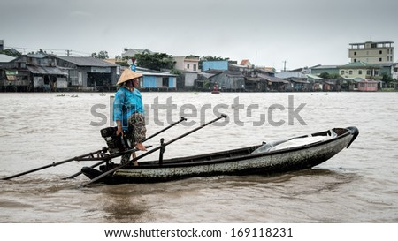 CAN THO, VIETNAM - JULY 29 2013: Vietnamese lady steers her boat in the rain towards the Phong Dien floating market in the Mekong delta 20km south west of Can Tho  - stock photo