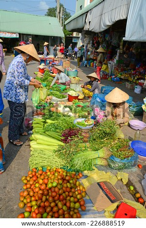 CAN THO, VIETNAM - MARCH 19, 2014: A lady buys vegetables from a street stall near the covered market in Can Tho, southern Vietnam, on the Mekong River Delta.