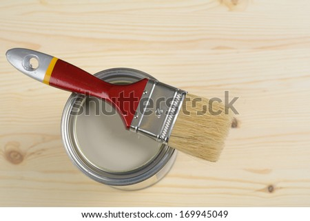 Can with paint and a paintbrush against wooden surface - stock photo