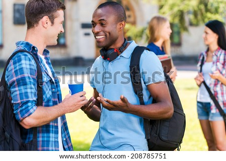 Can you believe it? Two young men talking to each other and smiling while two women standing in the background - stock photo