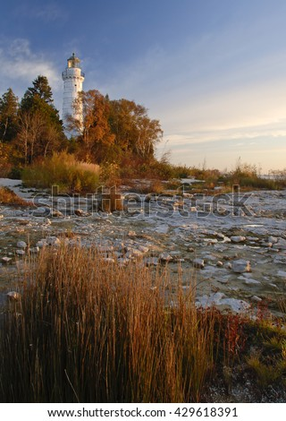 Cana Island Light is seen just after dawn in October with fall colors shinning almost as bright as the light, Cana Island Lighthouse, Door County, Wisconsin - stock photo