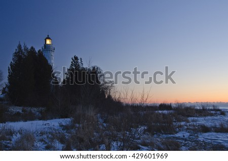 Cana Island Lighthouse shines into the predawn light in Door County, Wisconsin.  The light turns off automatically just before sunrise each day. - stock photo