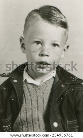 CANADA - CIRCA 1950s: An antique photo shows portrait of a freckled boy in denim jacket - stock photo