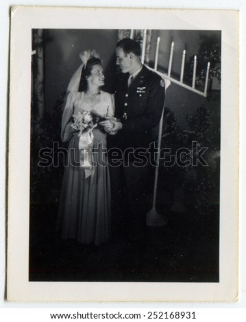 CANADA - CIRCA 1940s: Reproduction of an antique photo shows Bride and groom posing in the synagogue on the background of a menorah, the groom is a military pilot of the US Air Force - stock photo