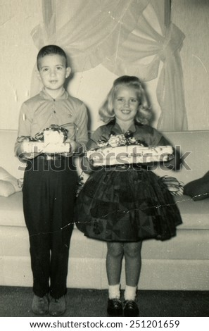 CANADA - CIRCA 1950s: Reproduction of an antique photo shows girl and boy posing with Christmas gifts in his hands - stock photo