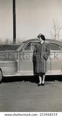 CANADA - CIRCA 1940s: Reproduction of an antique photo shows young woman in a fur coat and astrakhan hat posing near a luxury car - stock photo