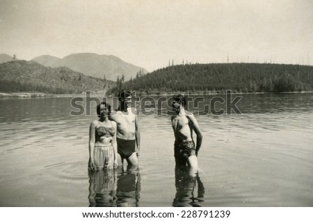 CANADA - CIRCA 1940s: Vintage photo shows two guys and devshki swimming in the river. - stock photo
