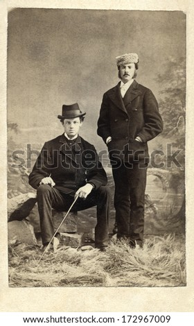 CANADA - HALIFAX - CIRCA 1870 - A vintage Cartes De Visite photo two young men. One is sitting on rock and one is standing. They are wearing suits with hats. Photo from the Victorian era. CIRCA 1870 - stock photo