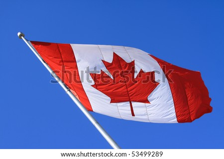 Canada maple leaf flag with blue sky background.