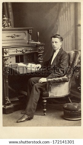 CANADA - MONTREAL - CIRCA 1868 A vintage Cartes de visite photo of a young gentleman. The man is sitting in front of a desk with a book. A photo from the Victorian era. CIRCA 1868  - stock photo