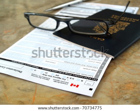 Canada passport on declaration card with glasses and pen - stock photo