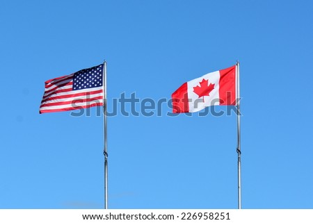 Canadian and USA flags flap in the breeze saluting each other. - stock photo