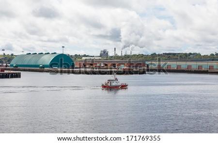 Canadian Coast Guard boat cruising past industrial area on coast of Canada - stock photo