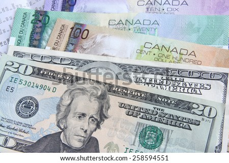 Canadian dollars vs. US dollars, which are important for board trading (manual focus) - stock photo