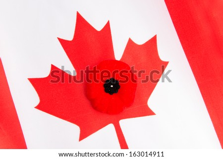 Canadian flag and a red poppy. The red poppy is the Canadian sign of remembering our veterans. Worn on the left side close to the heart, the poppy has become a symbol of Remembrance Day in Canada - stock photo
