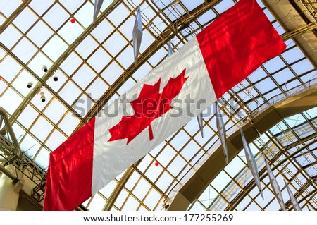 Canadian flag and building in the background - stock photo