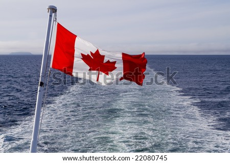 Canadian flag blowing in the wind against blue sky