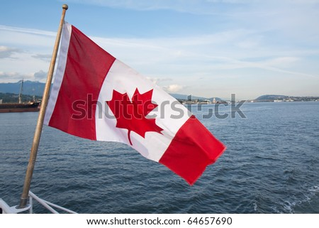 Canadian flag flies from a taffrail pole with a bit of motion blur over the bay near Vancouver - stock photo