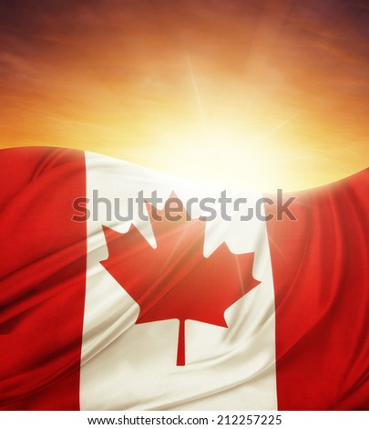 Canadian flag in front of bright sky - stock photo