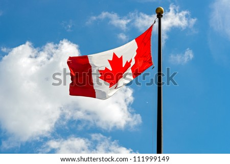 Canadian Flag in front of vivid, sunny, cloudy sky - stock photo