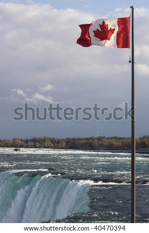 Canadian flag, Niagara Falls from Canada side - stock photo
