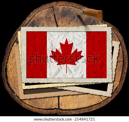 Canadian Flag on Section of Tree Trunk. Flag of Canada in a old photo frame on a section of tree trunk isolated on black background - stock photo