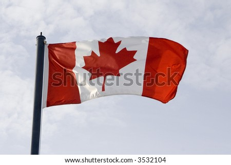 Canadian flag waving in the breeze in the sunshine against a blue sky