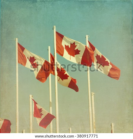Canadian flags.  Cross processed to look like a vintage picture with texture. - stock photo