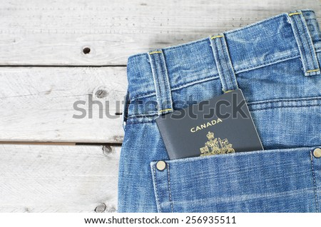 Canadian passport in blue jeans back pocket against wooden background - stock photo