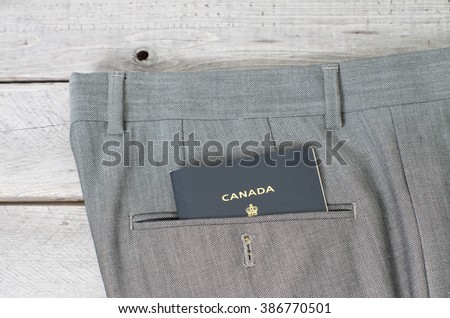 Canadian passport in grey pant back pocket against wooden background, white collar concept - stock photo