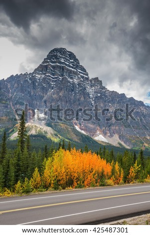 Canadian Rockies, Banff National Park in the autumn. Bright orange bush beside the road. Majestic mountains and glaciers on the background of cloudy sky - stock photo