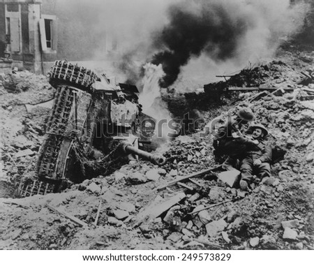 Canadian soldier is attended by a medic near Falaise, France. A burning overturned German tank is the in rubble nearby, during the Battle of the Falaise Pocket. August 6-17, 1944. - stock photo