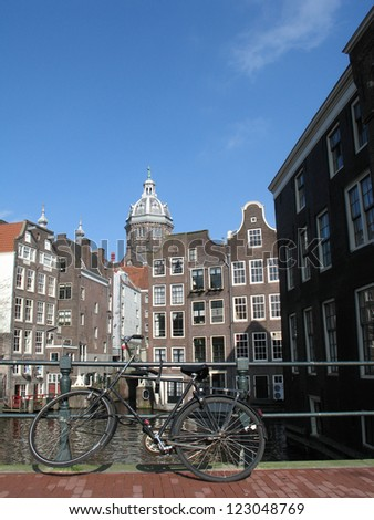 Canal and bridge in Amsterdam with bicycle - stock photo