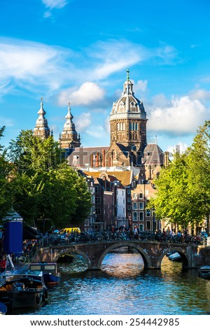 Canal and St. Nicolas Church in Amsterdam. Amsterdam is the capital and most populous city of the Netherlands - stock photo