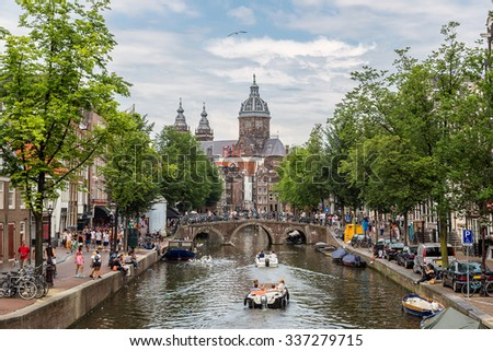 Canal and St. Nicolas Church in Amsterdam, Netherlands in a summer day