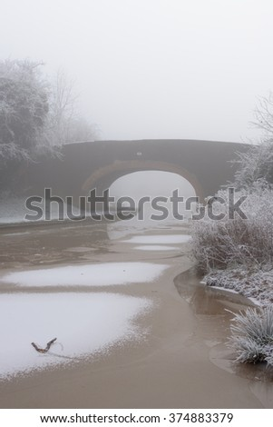 Canal Bridge covered in frost on a cold and foggy Winters day - stock photo