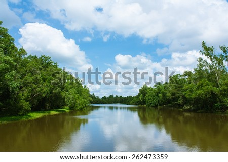 canal green tree and blue sky white cloud - stock photo