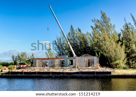 Canal Home Under Construction. Crane lifting trusses onto roof. - stock photo