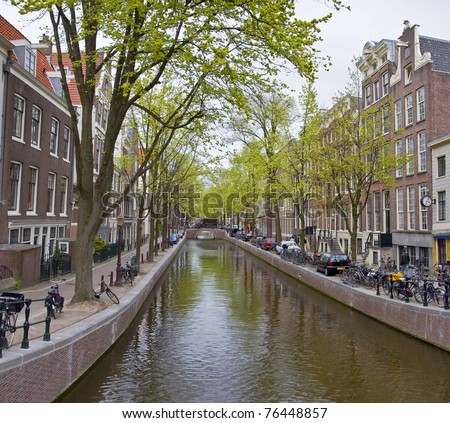 Canal in Amsterdam. Spring cityscape. Bicycles are on the waterfront. - stock photo