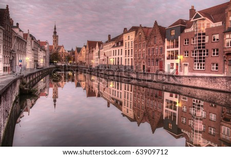 Canal in Bruges, Belgium, at dawn with the street ligts still burning, and lit by a rare pink sky filled with little clouds - stock photo