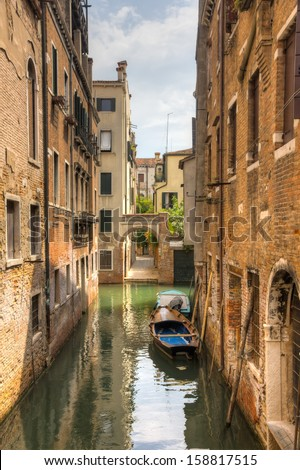 Canal in venezia with a boat in the middle